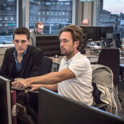 Två killar som sitter framför en datorskärm och diskuterar