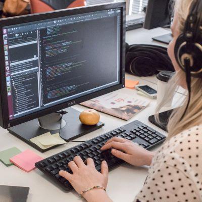 Bild på tjej med hörlurar som sitter vid en dator och skriver kod