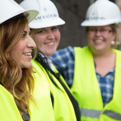 Tre tjejer i byggutrustning