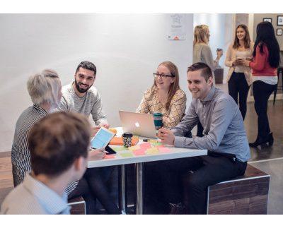 bild på studenter som sitter vid ett bord och pratar