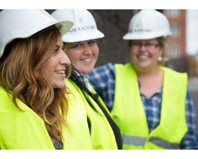 tre tjejer i byggnadsutrustning